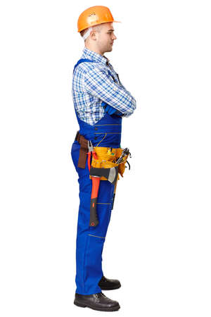 Full length side view portrait of young male construction worker wearing protective clothes, helmet and tool belt isolated on white background photo
