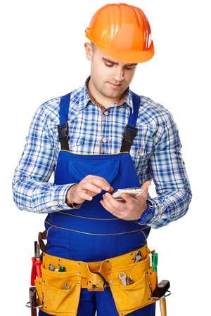 Chân dung của thanh niên công nhân xây dựng nam với điện thoại thông minh mặc quần áo bảo hộ, mũ bảo hiểm và vành đai công cụ phân lập trên nền trắng