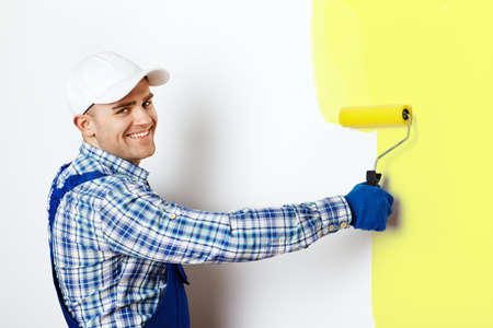 Happy young male painter painting a wall photo