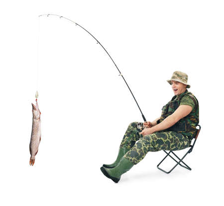 Young happy fisherman in camouflage catching a fish sitting on a chair isolated on white background