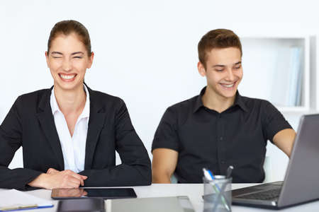 Two young cheerful businesspeople sitting at table in office and laughing photo