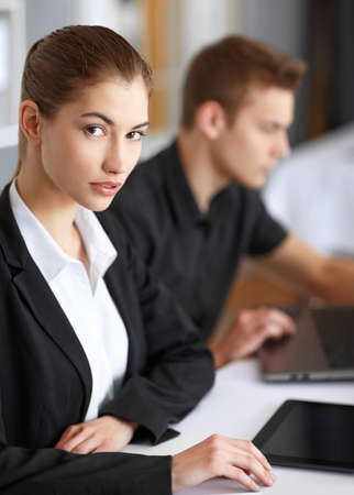 Two beautiful young businesspeople sitting at table in office and working at laptop and tablet pc photo