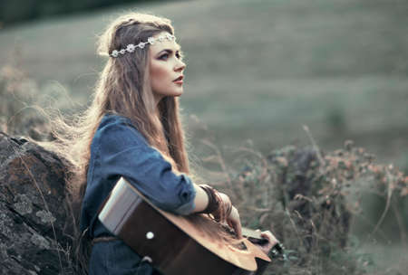 Beautiful hippie girl with guitar sitting on grass near stone