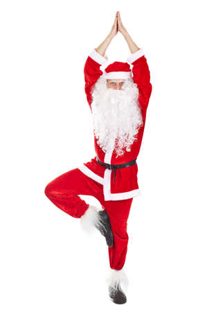 Happy Christmas Santa Claus doing yoga exercise tree-pose isolated on white background Stock Photo