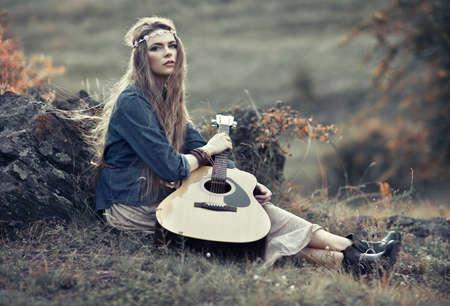 Beautiful hippie girl with guitar sitting on field near stone