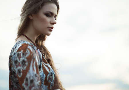 Dramatic portrait of beautiful hippie girl outdoors. Boho fashion style