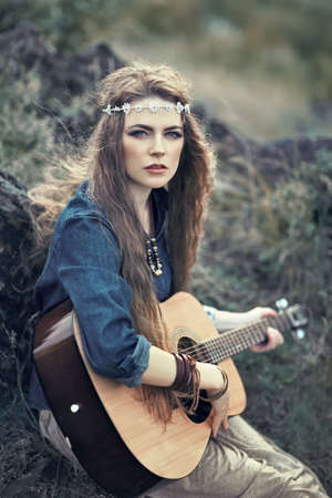 ethno: Beautiful hippie girl with guitar sitting on grass near stone