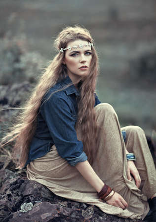 Beautiful hippie girl sitting on stone. Boho fashion style