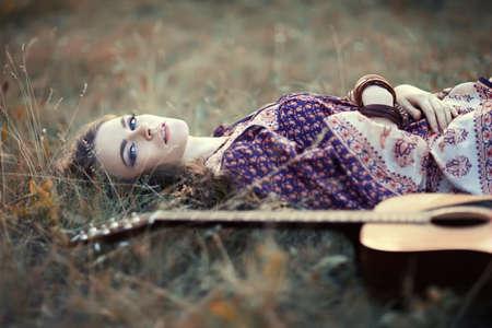 Đẹp hippie cô gái với cây đàn guitar nằm trên thảm cỏ