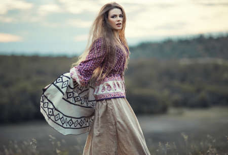 Beautiful hippie girl jumping outdoors at sunset. Boho fashion style Standard-Bild