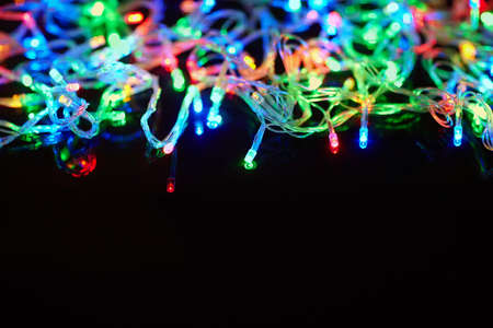 christmas illuminations: Christmas lights on black background with copy space. Decorative garland