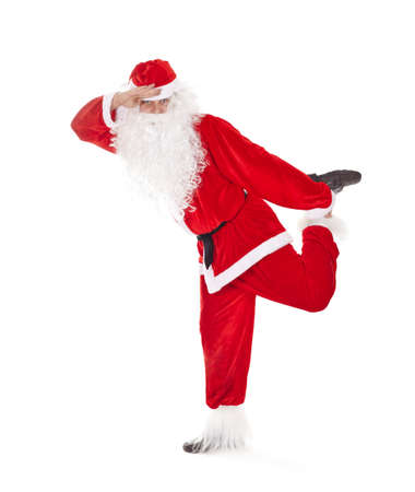 far away look: Happy Christmas Santa Claus having fun, standing on one leg and look far away, isolated on white background