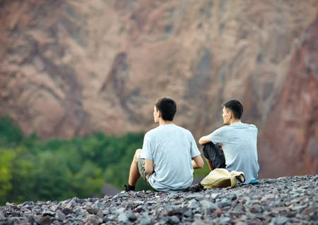 Two tourist young men sitting on rocky cliff and enjoying beautiful view Archivio Fotografico