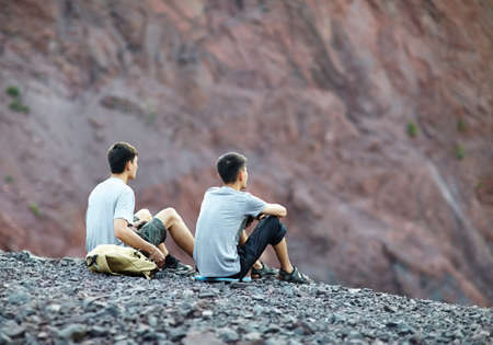 sitting on the ground: Two tourist young men sitting on rocky cliff and enjoying view