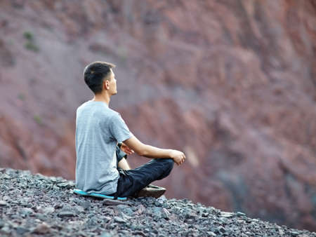 Young young man relaxing in yoga position on rocky cliff