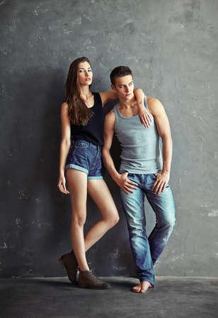 undershirt: fashion beautiful young couple on grey wall background
