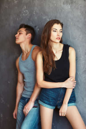 fashion beautiful young couple in quarrel on grey wall background photo