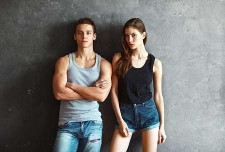 fashion beautiful young couple on grey wall background photo