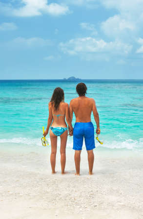 the topical: Couple on the beach with snorkel equipment. Young couple snorkeling together in a topical sea