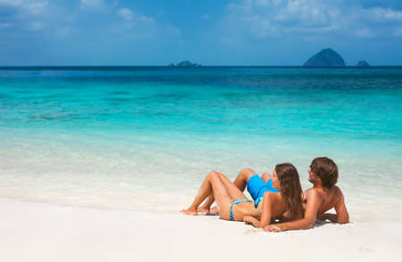 Young couple relaxing on the paradise beach