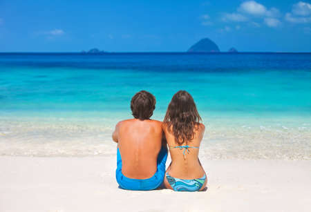 Young couple relaxing on the paradise tropical beach photo