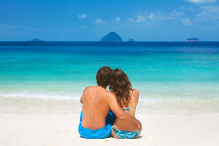 Young honeymoon couple sitting together on a sandy tropical beach