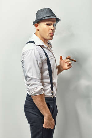 mafioso: Side view of a stylish young man smoking cigar Stock Photo