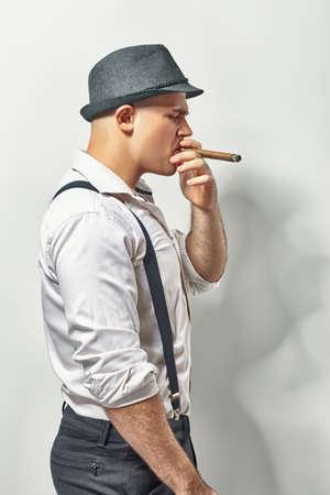 hombre fumando puro: Vista lateral de un hombre joven fumar cigarros con estilo