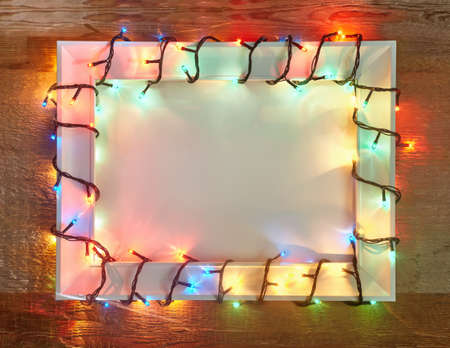 christmas illuminations: Christmas lights frame on wooden background with copy space. Decorative garland