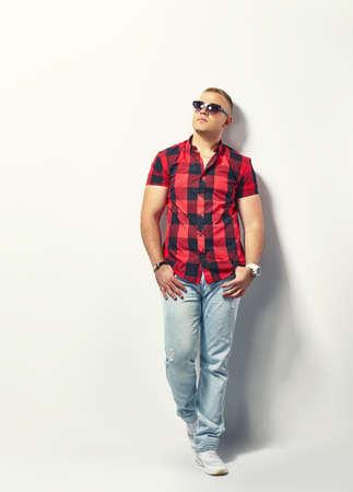 In voller Länge Porträt einer schönen stilvollen Mann in hipster kariertes Hemd und eine Sonnenbrille Standard-Bild