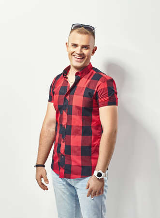 Fashion portrait of young smiling man in plaid shirt photo