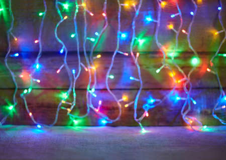 christmas lights background: Christmas lights on wooden background. Decorative garland
