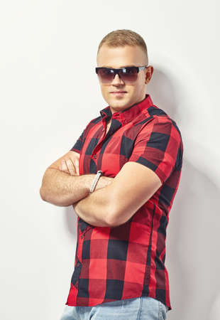Handsome stylish man in sunglasses and hipster plaid shirt photo