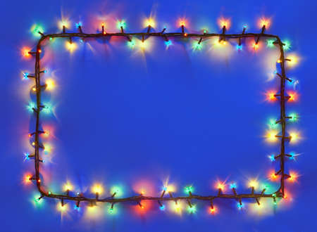 christmas light bulbs: Christmas lights frame on dark blue background with copy space. Decorative garland