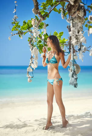 sexy female body: beautiful girl in bikini posing on the tropical beach under coral tree. Summer vacation