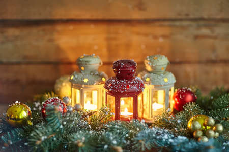 multicolored: Christmas lanterns and baubles in snow on wood background