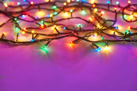 green frame: Christmas lights on dark pink background with copy space. Decorative garland Stock Photo