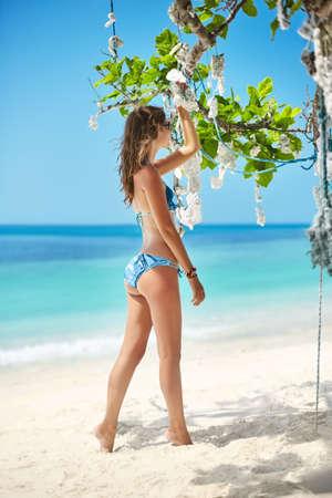 vacaciones en la playa: hermosa chica en bikini posando en la playa tropical bajo el árbol de coral. Vacaciones de verano