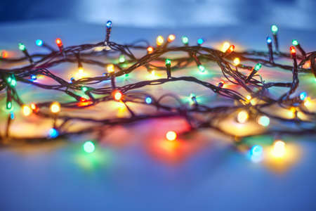 blue border: Christmas lights on dark blue background. Decorative garland Stock Photo