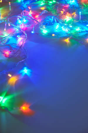 winter holiday: Christmas lights on dark blue background with copy space. Decorative garland