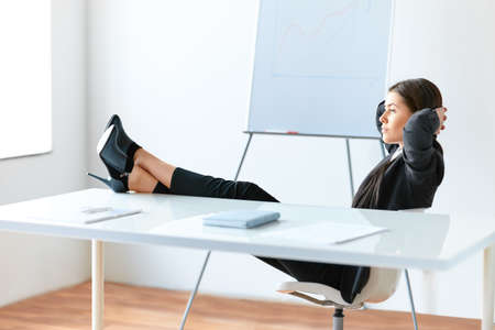 Portrait of relaxed pretty business woman sitting with legs on desk in the office Фото со стока