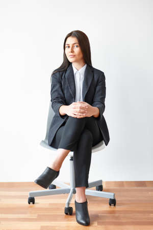Portrait of young business woman sitting on chair in the office