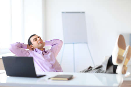feet relaxing: Portrait of relaxed businessman sitting with legs on desk in the office