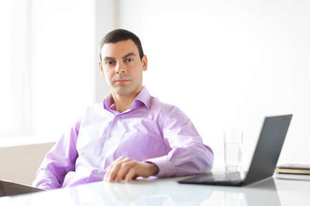 young executive: Portrait of young business man with laptop in the office Stock Photo