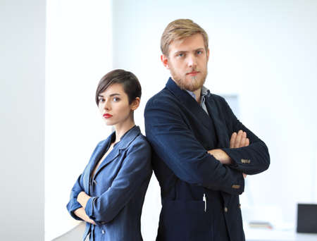 standing businessman: Businessman and businesswoman standing back to back with crossed arms in the office. Team work concept.