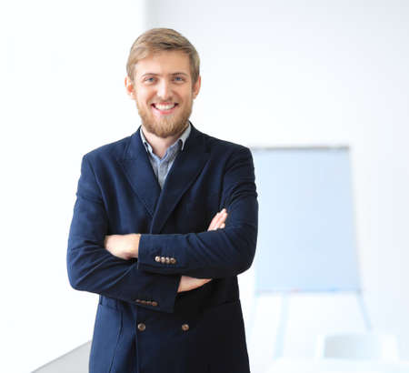 joyful businessman: Portrait of young successful businessman in the office. Crossed arms Stock Photo