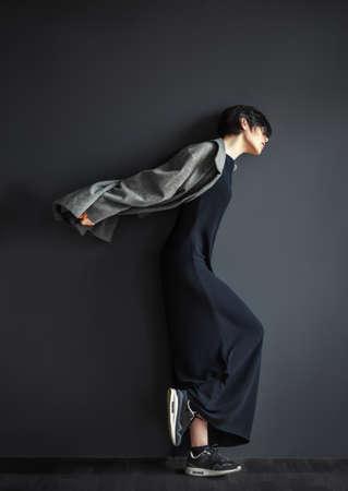 Solitaria chica de moda en movimiento sobre un fondo oscuro Foto de archivo - 54672004