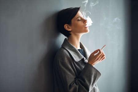 Portrait der modernen Frau, die eine Zigarette auf dunklem Hintergrund rauchen
