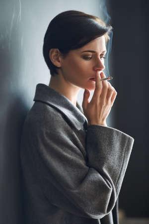 girls smoking: Portrait of fashionable woman smoking a cigarette on dark background Stock Photo