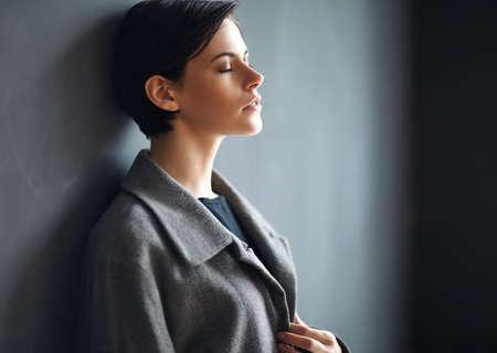 mujer pensativa: Portrait of tired beautiful woman on dark background